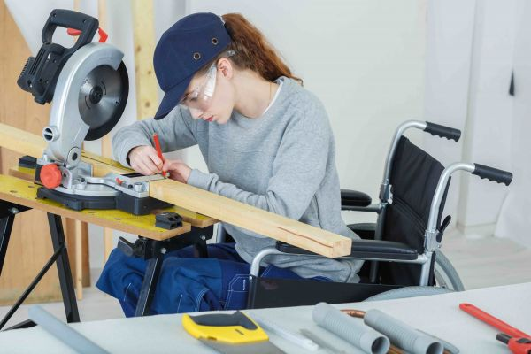 A woman in a wheelchair using tools